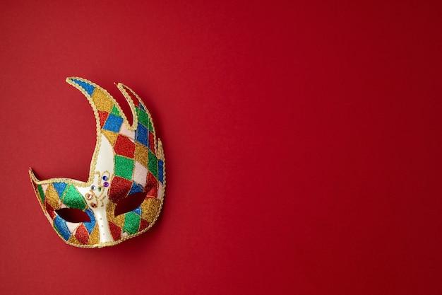 Festliche, bunte karneval- oder karnevalsmaske und accessoires über roter wand. flache lage, draufsicht, kopierraum