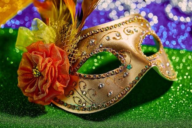 Festliche bunte karneval- oder karnevalsmaske und perlen auf goldgrün- und purpurhintergrund schließen venezianische masken-partyeinladungsgrußkarte venezianisches karnevalsfeierkonzept