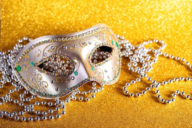 Festliche bunte karneval- oder karnevalsmaske und -perlen auf venezianischem masken-partyeinladungsgrußkarten-venezianischem karneval-feierkonzept des goldenen hintergrunds
