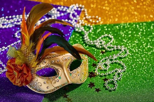 Festliche bunte karneval- oder karnevalsmaske und -perlen auf venezianischem masken-partyeinladungsgrußkarten-venezianischem karnevals-feierkonzept des goldgrün- und purpurhintergrundes
