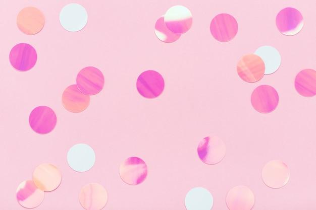 Festliche bunte konfetti auf pastellrosa hintergrund
