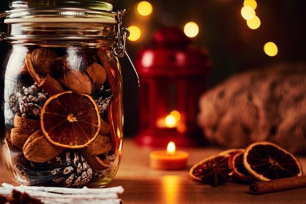 Festliche dekorationen. glasgefäß mit kiefernkegeln und getrockneten orangen auf einem hintergrund der feenhaften lichter