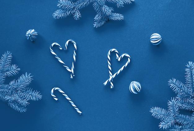 Festliche einfarbige blaue farbe weihnachten. flach liegend mit tannenzweigen, zuckerstangen als herzen, glaskugeln und trockenen limettenfrüchten. trendy null abfall.