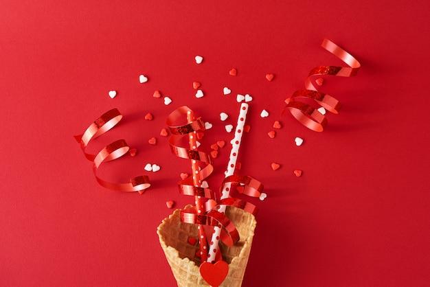 Festliche eistüte mit dekorationen und konfetti auf rotem backgrond, draufsicht flach gelegt. kreatives minimalismuskonzept
