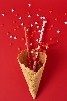 Festliche eistüte mit dekorationen und konfettis auf rotem backgrond, draufsichtebenenlage. kreatives minimalismuskonzept