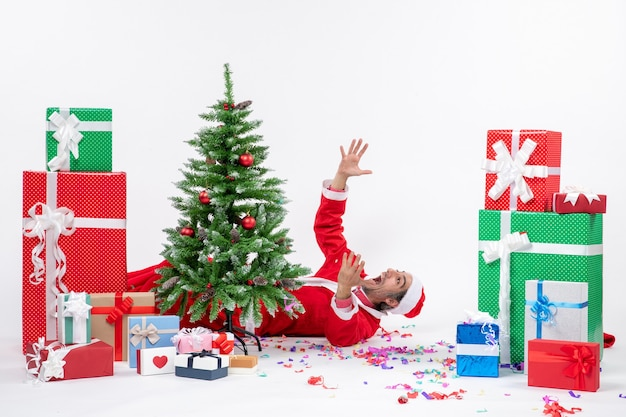 Festliche feiertagsstimmung mit jungem nervösem weihnachtsmann, der hinter weihnachtsbaum nahe geschenken auf weißem hintergrund liegt