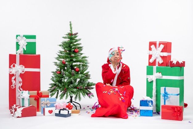 Festliche feiertagsstimmung mit lustigem positivem weihnachtsmann, der auf dem boden sitzt und mit weihnachtsdekorationen nahe geschenken und geschmücktem weihnachtsbaum auf weißem hintergrund spielt