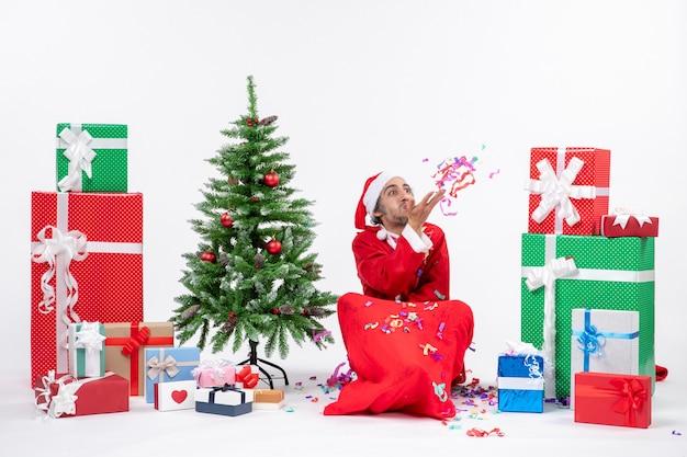 Festliche feiertagsstimmung mit lustigem weihnachtsmann, der auf dem boden sitzt und mit weihnachtsdekorationen nahe geschenken und geschmücktem weihnachtsbaum auf weißem hintergrund spielt