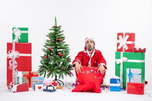 Festliche feiertagsstimmung mit traurigem weihnachtsmann, der auf dem boden sitzt und mit weihnachtsdekorationen nahe geschenken und geschmücktem weihnachtsbaum auf weißem hintergrund spielt