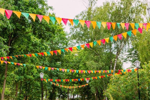 Festliche flaggen, die draußen an einem klaren sommertag hängen. dekorationen von bunten flaggen für feier