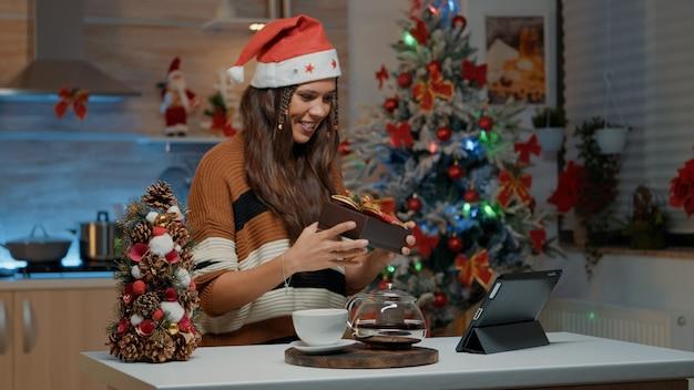 Festliche frau, die geschenk auf videoanrufkamera empfängt