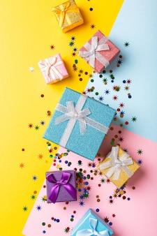 Festliche gelbe oberfläche mit bunten geschenkgeschenken. grußkartenkonzept für geburtstag, weihnachten, karneval. kopierraum, draufsicht, flache lage