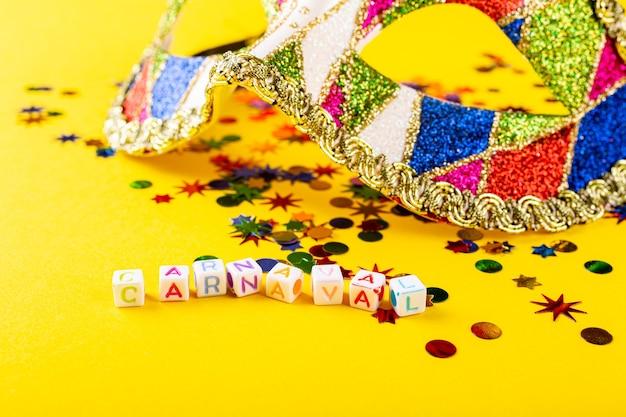 Festliche gelbe oberfläche mit bunten karnevalsmaskenwürfeln mit holländischem text carnaval. grußkartenkonzept für karneval und party. kopierraum, selektiver fokus