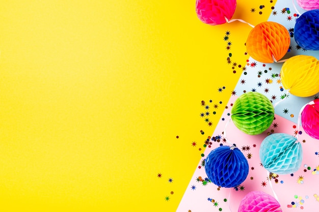 Festliche gelbe oberfläche mit bunten papierkugeln. grußkartenkonzept für geburtstag, party, einladung, karneval. kopierraum, draufsicht, flache lage