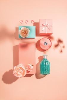 Festliche geometrische anordnung von geschenkboxen und blumen in pastellfarben mit sonnigen schatten