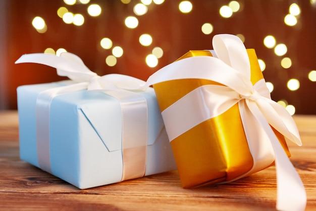 Festliche geschenkbox auf holztisch gegen braunes bokeh