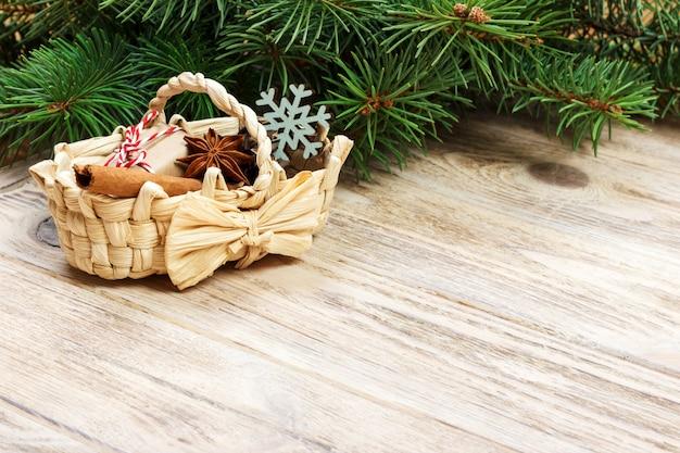 Festliche geschenke mit kästen, sternanis, korb, zimt und schneeflocke auf hölzernem hintergrund. weihnachtsgeschenke mit exemplar