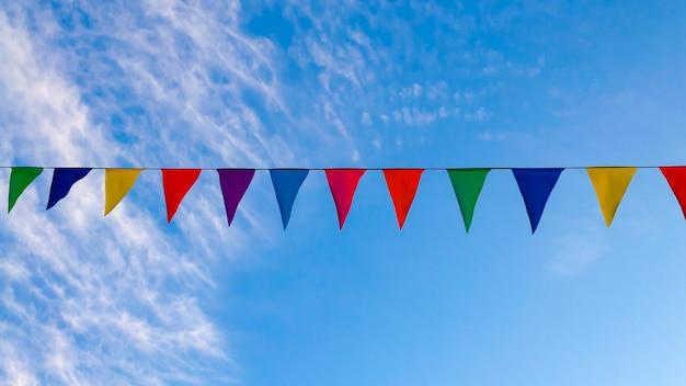 Festliche girlanden, flatternde farbige bänder, blauer himmel hintergrund, website-cover über fröhliche stimmung, festival.