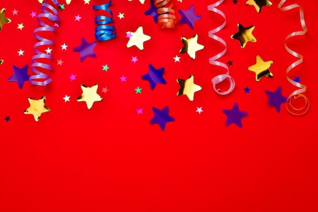 Festliche goldene und lila konfetti-sterne auf rotem grund