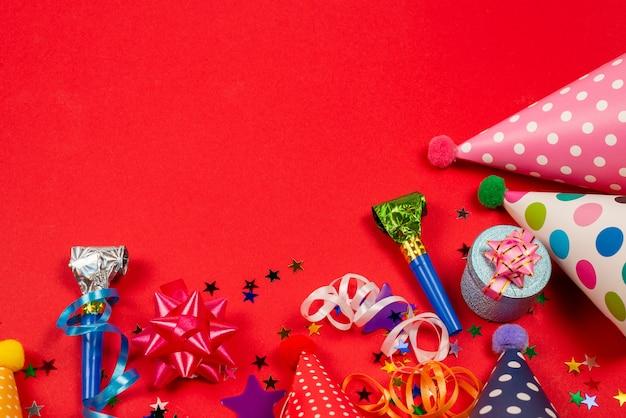 Festliche goldene und lila konfetti-sterne und ein geschenk, geburtstagskappen auf rotem grund. platz für text oder design.
