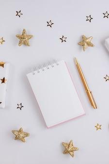 Festliche goldene verzierungen und leeres notizbuch auf weißem hintergrund. flach liegen. planungskonzept.