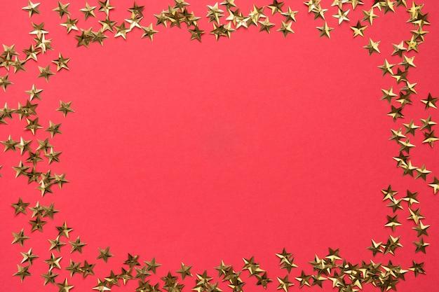 Festliche grenze von goldenen sternfunkelnkonfettis auf rotem hintergrund. weihnachtsfeiertag.