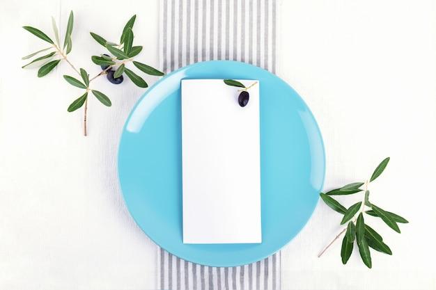 Festliche hochzeit, geburtstagsgedeck mit goldenem tischbesteck, ölzweig, pastellblaue porzellanteller. leere karte. restaurant menükonzept