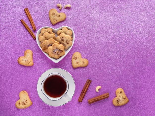 Festliche ingwerplätzchen mit zimt in form von herzen werden mit einer tasse tee auf eine rosa oberfläche gelegt. draufsicht.