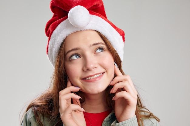 Festliche kappe der glücklichen mädchenporträt-nahaufnahme mit rundem pompon. hochwertiges foto