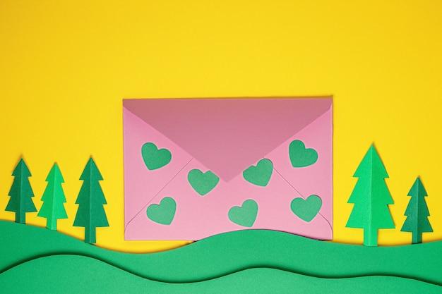 Festliche karte. grüne papierherzen und rosa umschlag auf gelbem hintergrund. kreativer papierschnitthintergrund mit papierumschlag. papierkunst am valentinstag, geburtstag, hochzeit. flach legen, platz kopieren