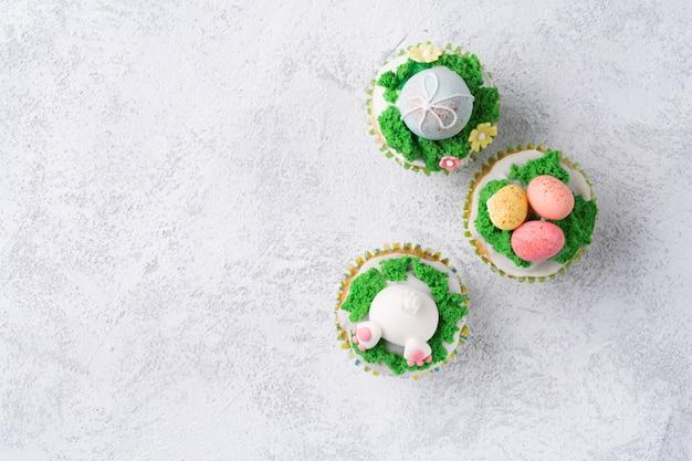 Festliche kleine kuchen mit lustigem häschen, eiern und gras auf weißem hintergrund. ostern-feiertagskonzept. draufsicht mit kopienraum