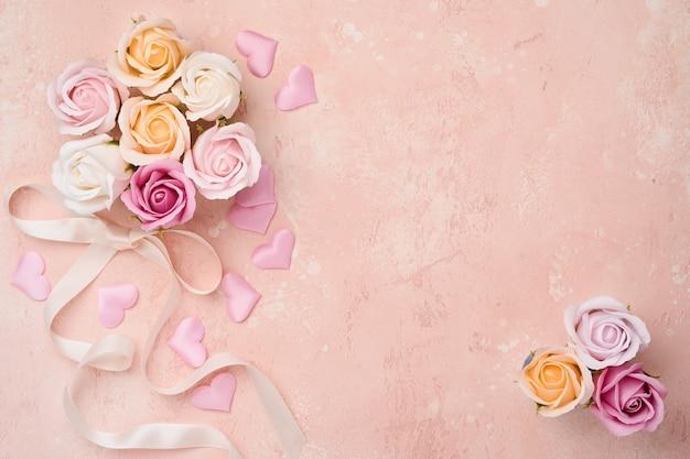 Festliche komposition mit schönen zarten rosenblumen in der rosa runden schachtel auf hellrosa tisch. flache lage, kopierraum.