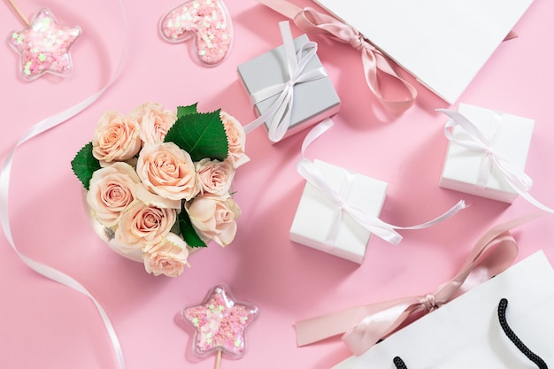 Festliche komposition mit strauß rosa rosen in vase, funkelnden dekorationen, geschenkboxen