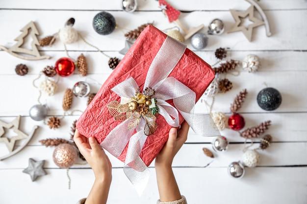 Festliche komposition mit weihnachtsgeschenk auf unscharfem weißem hintergrund mit dekorations-draufsicht.