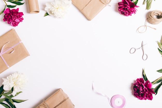 Festliche komposition von pfingstrosen und geschenken auf weißem tisch
