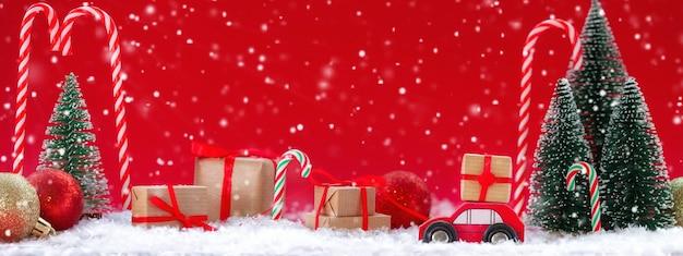 Festliche komposition weihnachtsrotes auto mit einer geschenkbox in einem kiefernwald, wo viele verschiedene geschenke auf rotem hintergrund sind. frohes neues kartenkonzept. banner.