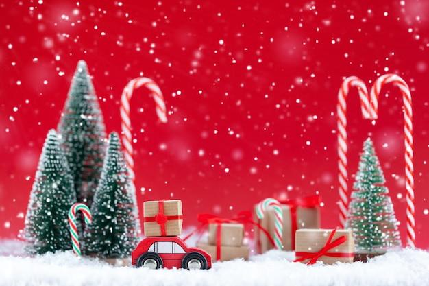 Festliche komposition weihnachtsrotes auto mit einer geschenkbox in einem kiefernwald, wo viele verschiedene geschenke auf rotem hintergrund sind. frohes neues kartenkonzept.