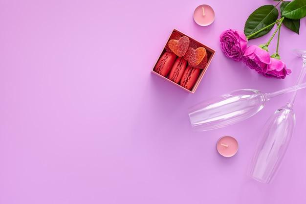 Festliche komposition zum valentinstag. rosa rose, schachtel mit makronen und gläsern