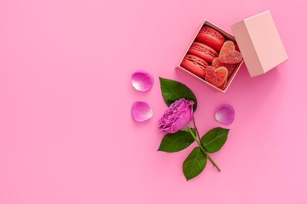 Festliche komposition zum valentinstag rosa rose, schachtel mit makronen