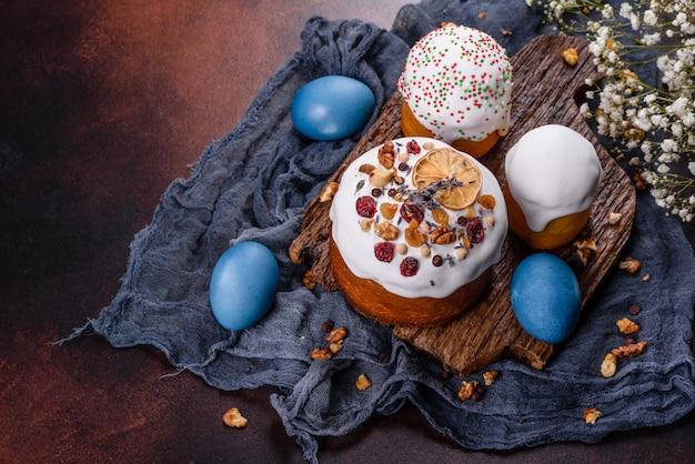 Festliche kuchen mit weißer glasur, nüssen und rosinen mit ostereiern auf dem festlichen tisch. vorbereitungen für ostern