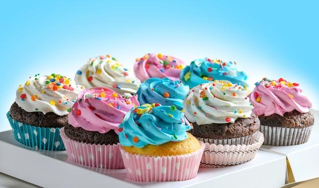 Festliche leckere cupcakes im lieferkarton für party, verschiedene cupcakes mit rosa weißer und blauer creme auf blauem hintergrund. platz kopieren