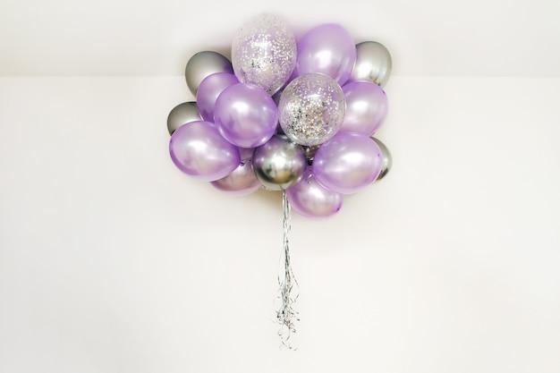 Festliche lila und silberne luftballons fliegen unter der decke, festliches konzept