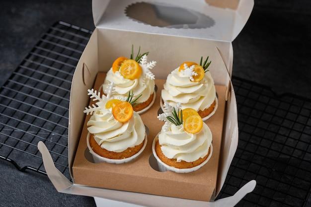 Festliche muffins mit frischkäsecreme und zitrusfüllung. süßwaren für den urlaub. dessert dekoriert mit kumquat, rosmarin und mastix-schneeflocken, verpackt in einer geschenkbox.