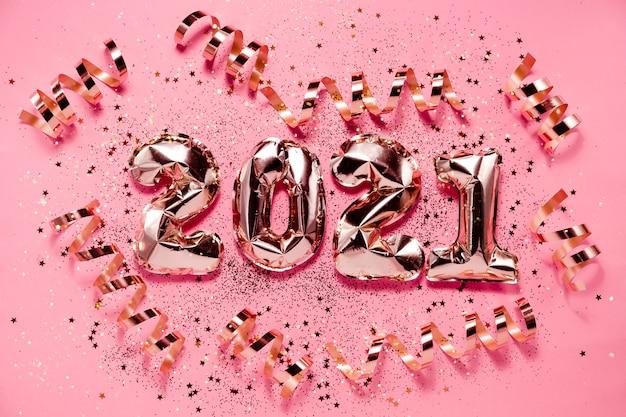 Festliche neujahr flatlay hintergrund roségold folie luftballons und weihnachten dekorationen. copyspace der horizontalen ansicht von oben.