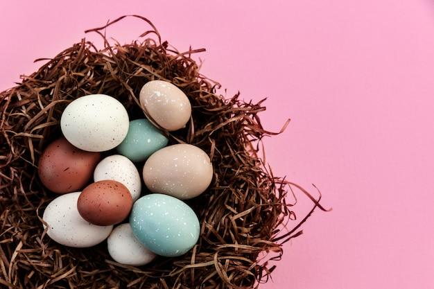 Festliche ostereier im nest gegen rosa hintergrund, traditionelle dekoration für zu hause am saisonalen feiertag