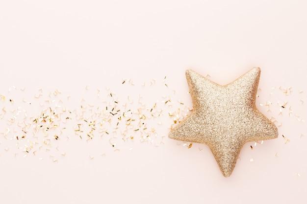 Festliche pastellhintergrund-weihnachtssterne und glänzender glitzer, konfetti auf pastellhintergrund.