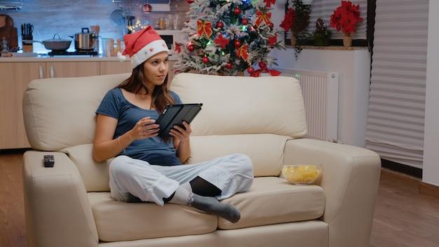 Festliche person, die an heiligabend an tablet arbeitet und fernsehen schaut