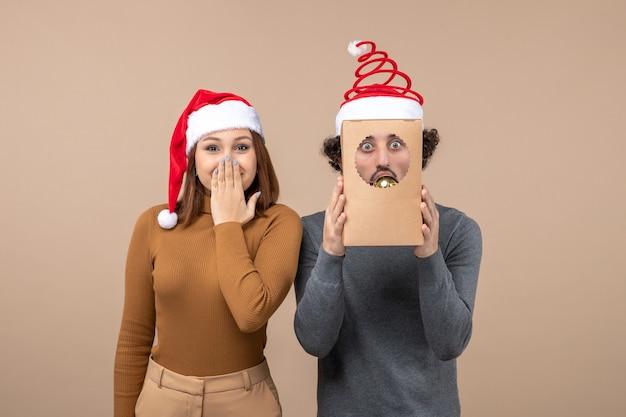 Festliche stimmung mit aufgeregtem coolem paar, das rote weihnachtsmannhüte auf grau trägt