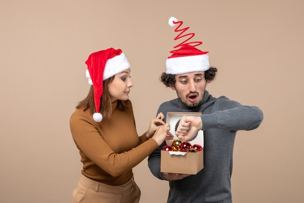 Festliche stimmung mit aufgeregtem coolem paar, das rote weihnachtsmannhüte auf grauem filmmaterial trägt