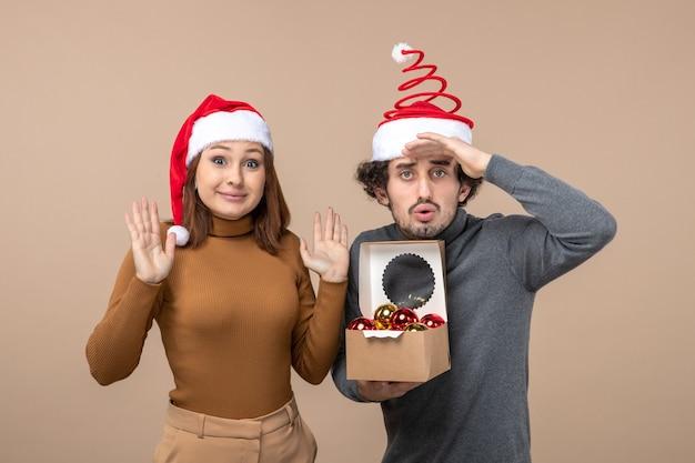Festliche stimmung mit aufgeregtem coolem paar, das rote weihnachtsmannhüte auf grauem lagerbild trägt